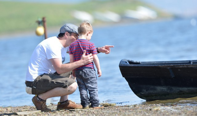 A father and his son stand on the coast by a boat near Moonfleet Manor hotel in Dorset
