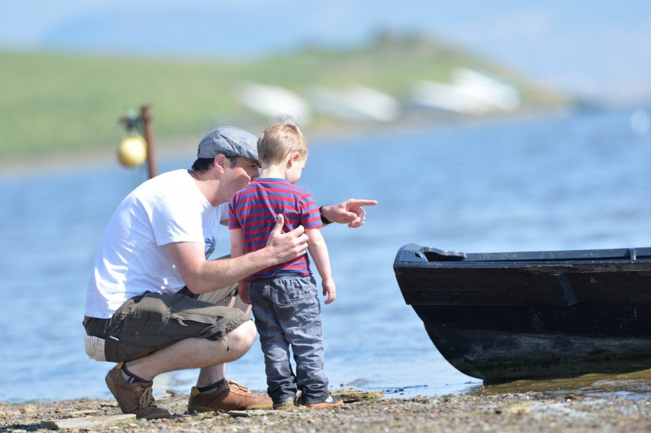 A father and son stand on the coast by a boat near Moonfleet Manor hotel in Dorset
