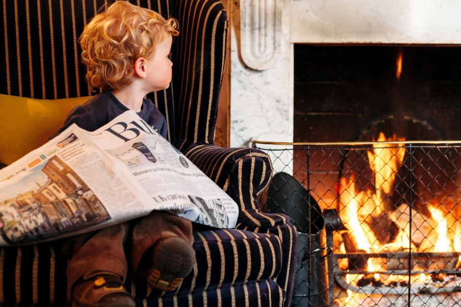 A boy sits by the fire with a newspaper at Moonfleet Manor luxury family hotel in Dorset