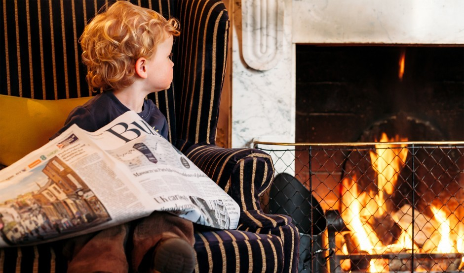 A boy sits by the fireside at Moonfleet Manor luxury family hotel in Dorset