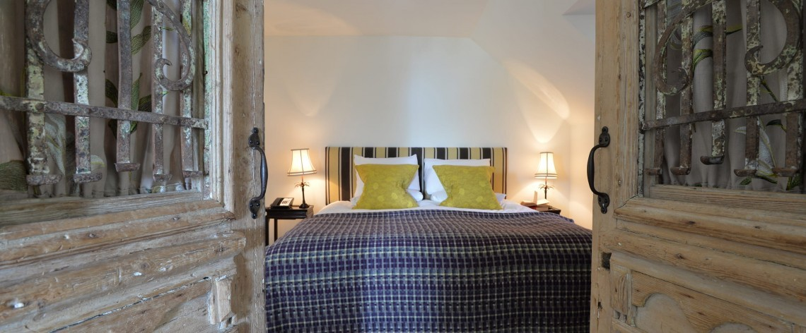 Ornate doors open onto a bedroom at Moonfleet Manor luxury family hotel in Dorset