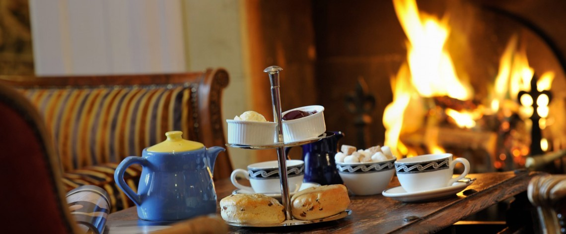 Afternoon tea laid out on a table by a roaring log fire.