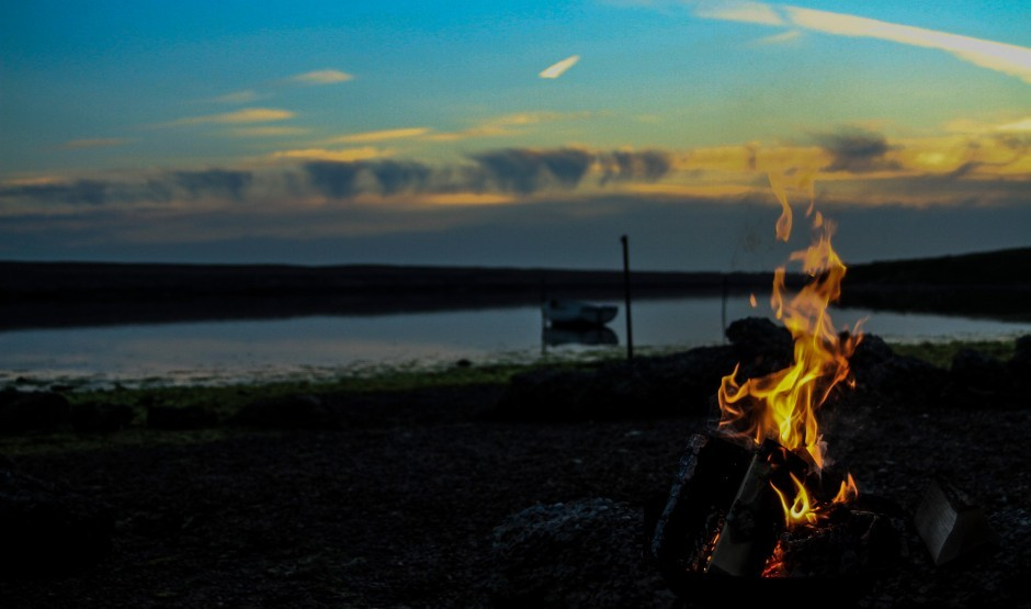 Sunset over the sea with a fire in the foreground.