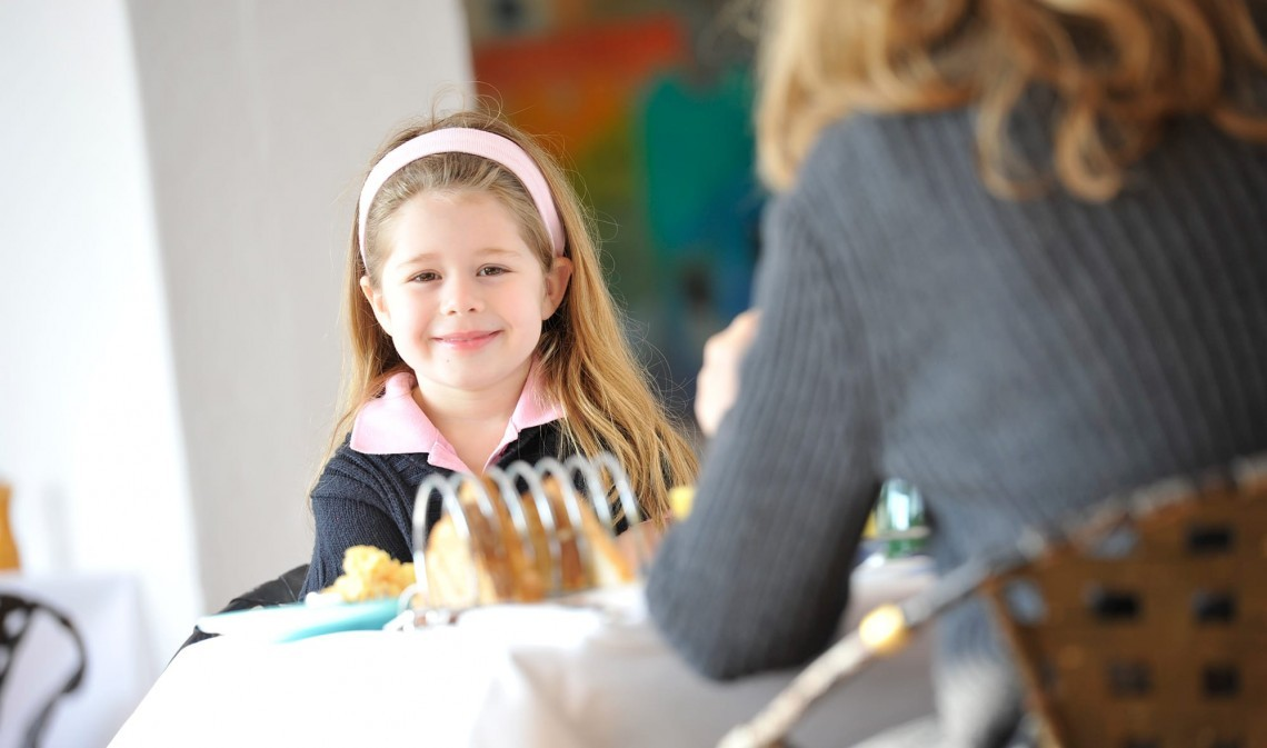 Child sat at the breakfast table with her mum at Moonfleet Manor restaurant.
