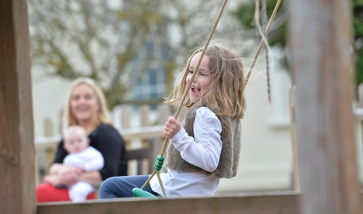 Young girl sat on a outdoor swing, with her mum and younger sibling in the background.