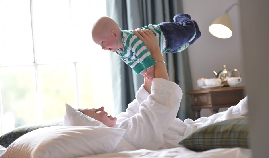 A mum lying in bed lifts her toddler son into the air.